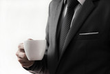 Business man offering cup of coffee.