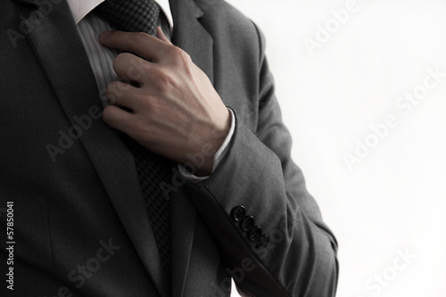 Business man adjusting his necktie