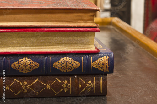 Antique Books with Gold Inlay Stacked on a Table