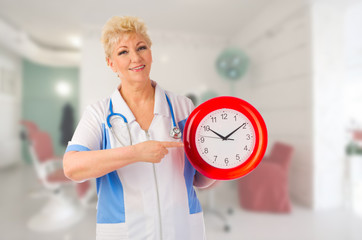 Mature doctor with clock
