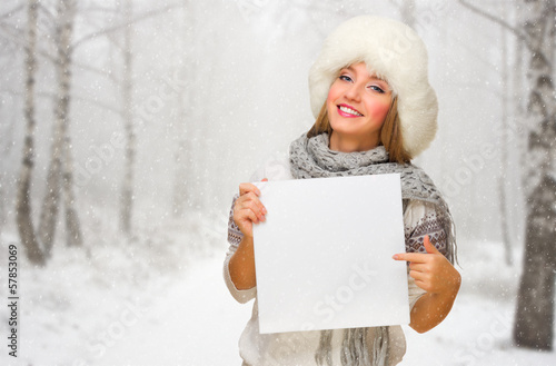 Girl with empty card at snowy forest