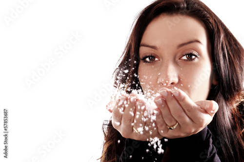 Young girl blowing snowflakes