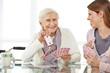 Leinwanddruck Bild Frau spielt mit Seniorin im Seniorenheim Karten