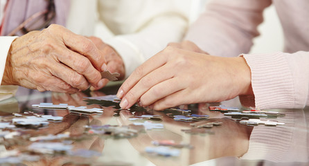 Hände von Seniorin und Frau mit Puzzle