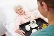 Seniorin im Pflegeheim bekommt Frühstück ans Bett