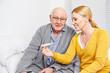 Frau und Senior schauen auf Fieberthermometer