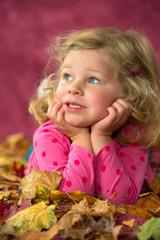 girl is lying in autumn foliage