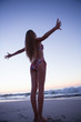 Woman enjoying the sunset with arms outstretched