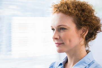 Thoughtful red hair businesswoman posing