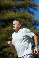 Cheerful retired man jogging