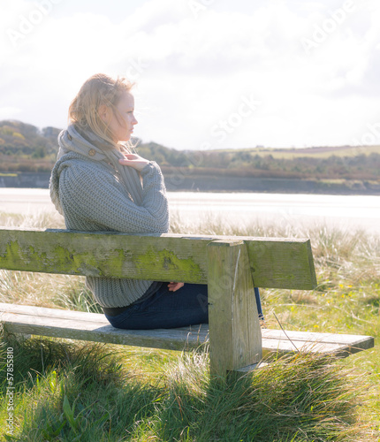 Pretty young woman sitting on a bench