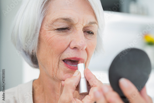 Mature woman using lipstick