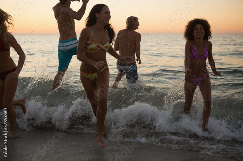 Friends playing and joking in the ocean at sunset