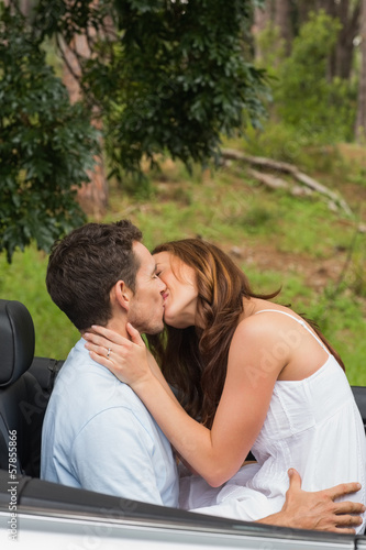Happy couple kissing on the backseat