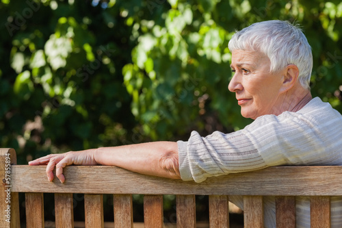 Pensive elderly woman sitting alone on a bench