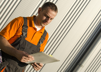 worker with paper folder in front of industrial hall