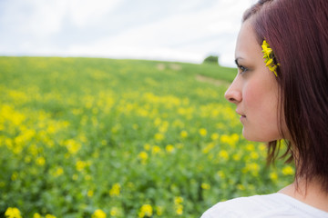 Brunette looking at field of yellow flowers
