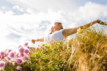 Woman feeling free in field of wild flowers
