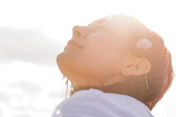 Woman with flower behind ear looking up to sky