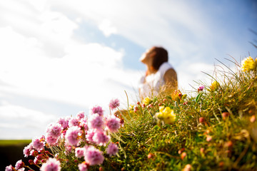 Woman sitting and thinking in field of wild flowers