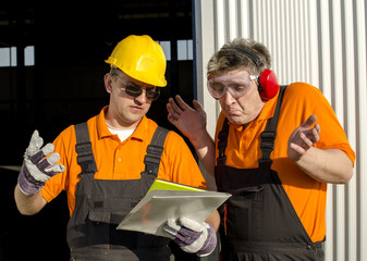 workes with paper folder in front of industrial hall