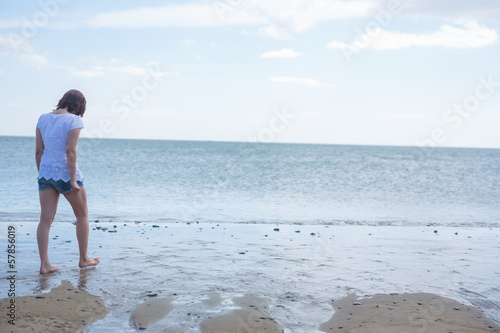 Woman in shorts walking out to sea