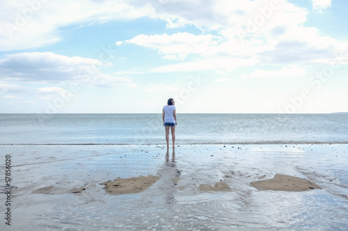 Woman in shorts strolling out to sea