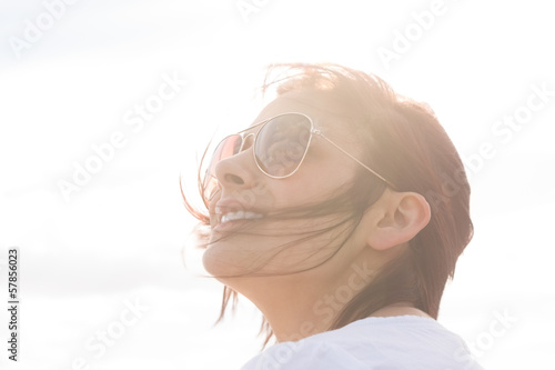Woman in sunglasses looking up at sky