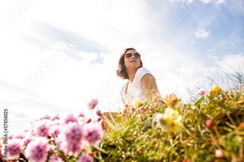 Woman sitting in field of wild flowers