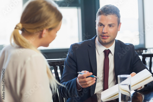 Businessman looking to associate with notepad and pen