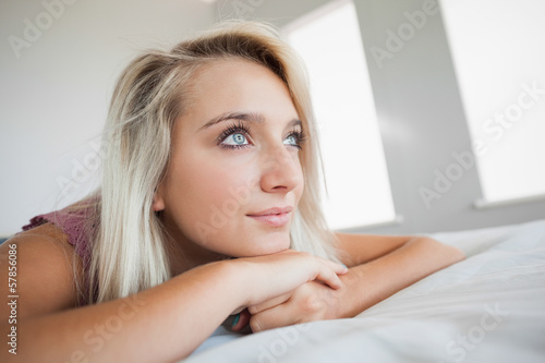 Gorgeous pensive blonde lying on bed looking away