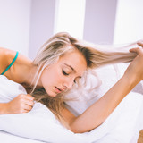 Gorgeous calm blonde lying on bed holding her hair
