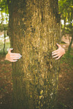 Picture of young woman embracing a trunk