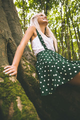 Low angle picture of smiling gorgeous blonde leaning against tree