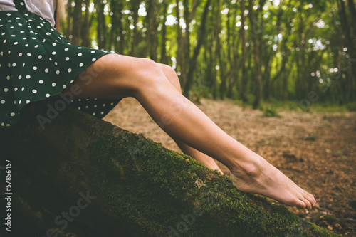 Legs of a woman wearing a dotted skirt sitting on tree