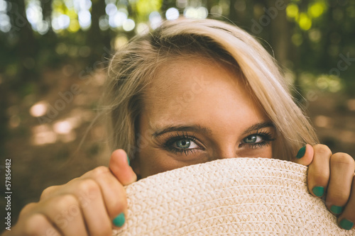 Happy gorgeous blonde holding straw hat in front of her face