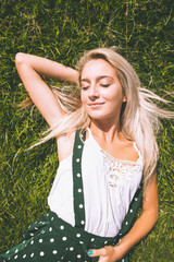 Peaceful gorgeous blonde lying on lawn with closed eyes