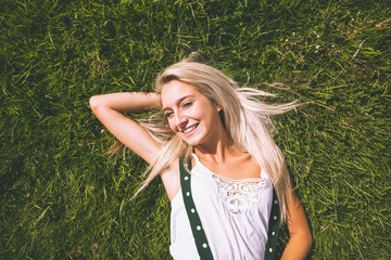 Smiling gorgeous blonde lying on lawn
