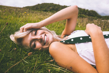 Cheerful gorgeous blonde lying on lawn