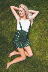 Cheerful gorgeous blonde lying on lawn with closed eyes