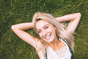 Happy gorgeous blonde lying on lawn