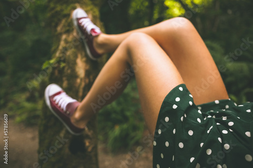 Picture of female legs lying on a tree