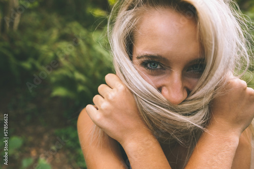 Happy gorgeous blonde covering her mouth with hair