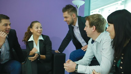 a group of people talking in the office