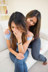 Distressed woman sitting on a couch being consoled by her sister