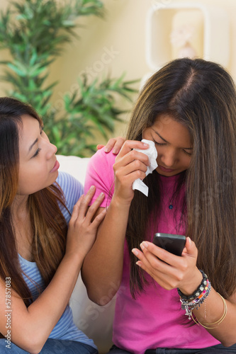 Crying woman sitting on a couch using her mobile phone being consoled by her sister