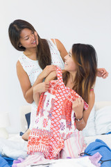 Two pretty sisters having fun while trying on some clothes