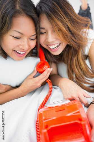 Two young sisters having fun with a telephone