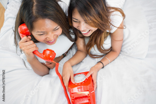 Two sisters making a call on an old fashioned dial phone