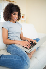Pretty smiling brunette typing on her laptop